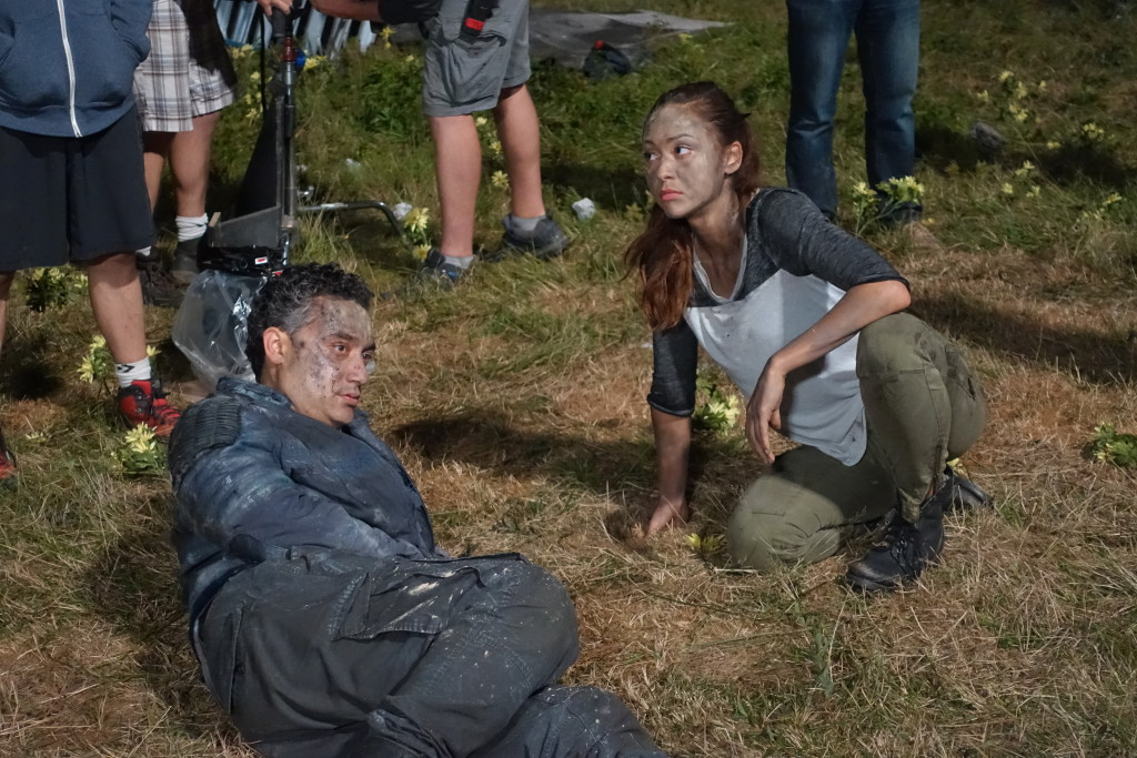 Lindsey Morgan (Raven) and Alessandro Juliani (Sinclair) blocking the explosion aftermath.